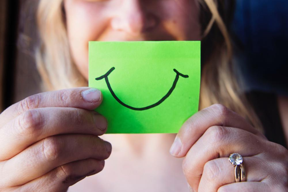 Woman holding post it note with smile on it | Gentle Dental Extractions in Fredericksburg | Smiley Face